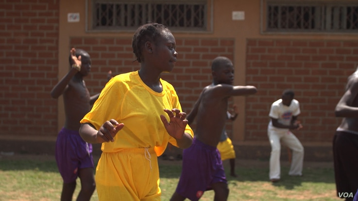 A young Central African Republic woman performs capoeira at an orphanage in Bangui. A group of refugees brought the martial back with them from the Democratic Republic of the Congo, April 20, 2017. (Photo: Z. Baddorf/VOA)