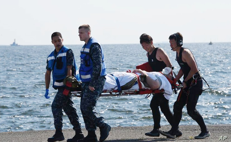 In this photo released by Japan's Defense Ministry, an injured USS Fitzgerald crew member is carried by U.S. military personnel, left, and Japanese Maritime Self-Defense Force members upon arriving at the U.S. naval base in Yokosuka, southwest of Tok...