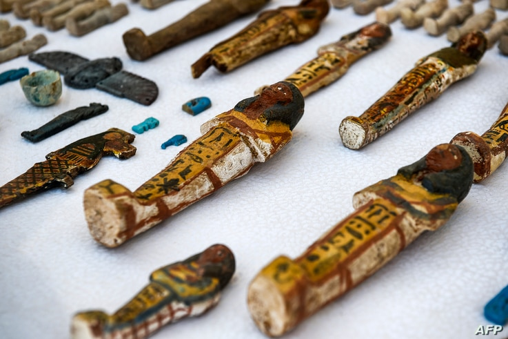 """This picture taken Nov. 24, 2018, shows carved wooden statues and funerary figurines called """"Ushabtis"""" made of wood, faience and clay, discovered by an Egyptian archaeological mission at the site of Tomb TT28 at Al-Assasif necropolis on the west bank..."""