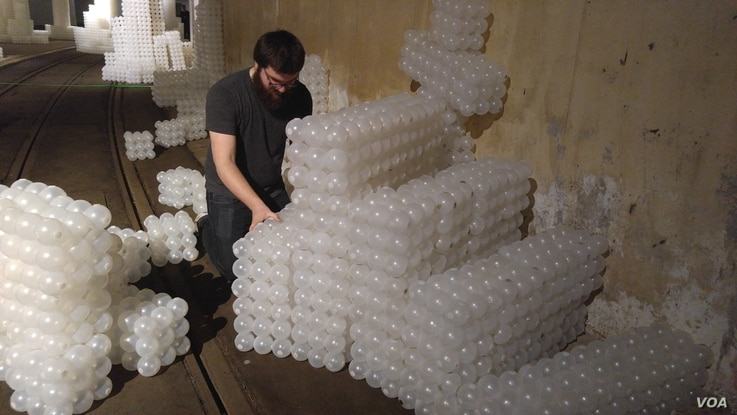 Alex Sceery building a spiral staircase with cubes made with plastic balls. (D. Block/VOA)