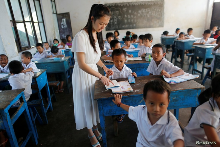 FILE - A teacher teaches Chinese language to kids in a school at Namtit, Wa territory in northeast Myanmar, Nov. 30, 2016.