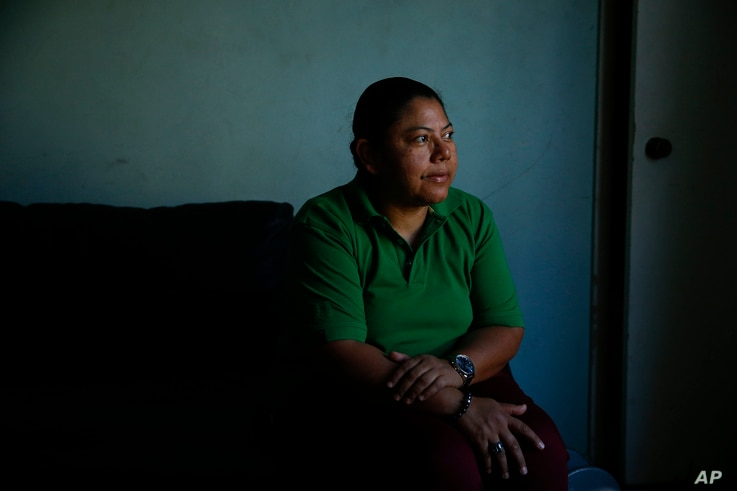 Iris Acosta, a 51-year-old hotel housekeeper from Honduras, pauses for photos in her sister's apartment in Los Angeles, Oct. 18, 2017.