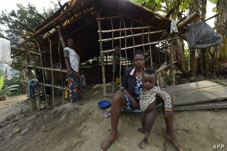 FILE - A Cameroonian refugee sit holding her child in front of a make-shift home, where hundreds are being sheltered, at Bashu-Okpambe village in Boki district of Cross Rivers State in southeast Nigeria, Jan 31, 2018.