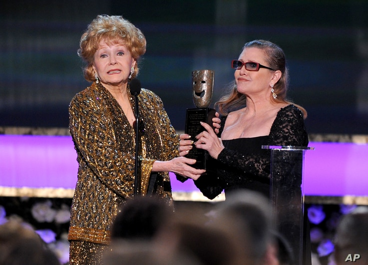 Carrie Fisher presents Debbie Reynolds with the Screen Actors Guild life achievement award at the 21st annual Screen Actors Guild Awards at the Shrine Auditorium, Jan. 25, 2015, in Los Angeles.