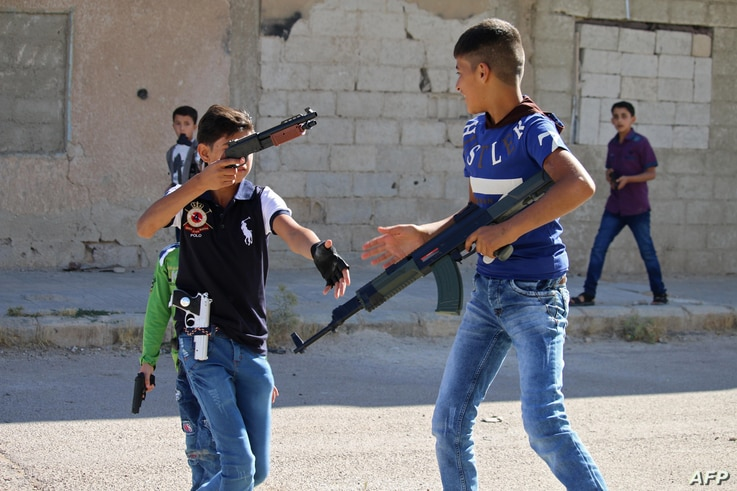 Syrian children play with fake plastic guns in the streets of Daraa, southern Syria, on June 15, 2018.
