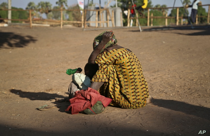 A South Sudanese refugee woman sits with her child at a refugee collection center in Palorinya, Uganda, Feb. 16, 2017.