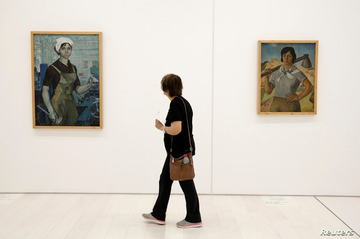 "A visitor walks past the paintings ""The Turner,"" left, by Albanian artist Zef Shoshi and ""The Action Worker"" by Hasan Nallbani during the Documenta 14 art exhibition in the National Museum of Contemporary Art in Athens, Greece, May 9, 2017."