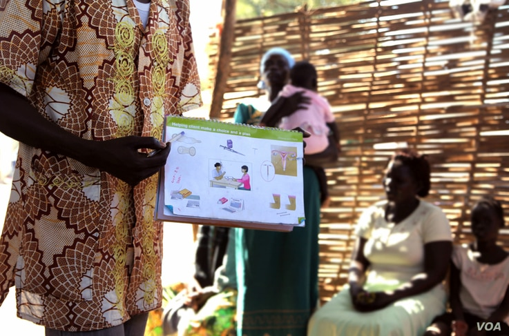 A health worker explains birth control at a clinic outside Juba, South Sudan. (H. McNeish for VOA)