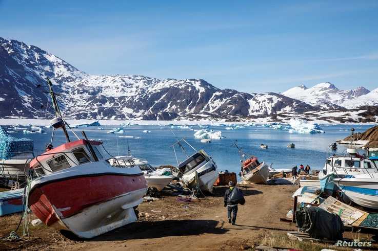 FILE PHOTO: A man walks to his boat past a number of abandoned and dry-docked boats in the town of Tasiilaq, Greenland, June 15, 2018.