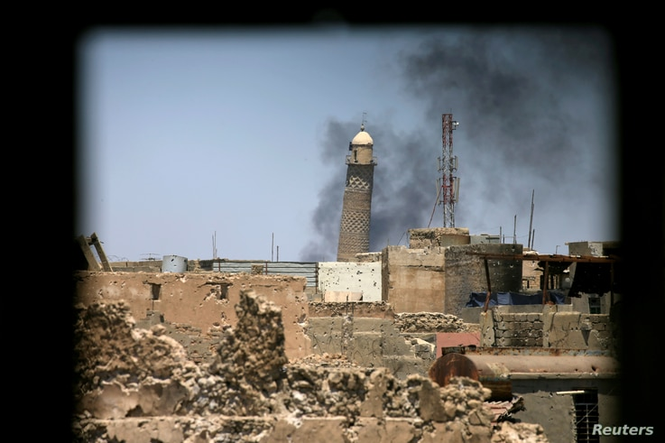 FILE - Al-Hadba minaret at the Grand Mosque is seen through a building window in the old city of Mosul, Iraq June 1, 2017.
