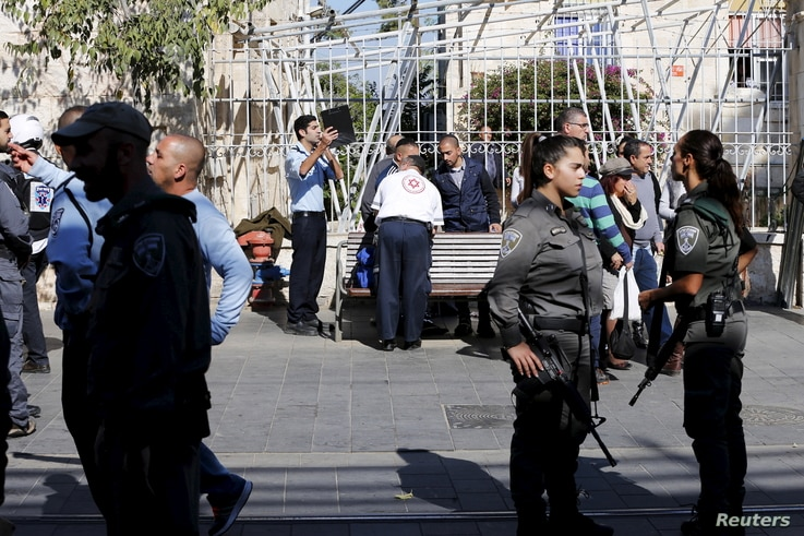 Israeli security personnel and medics stand at the area where a stabbing attack by two Palestinian women took place in central Jerusalem, Nov. 23, 2015.