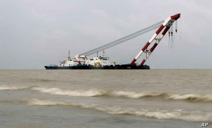A heavy lift offshore crane arrives for rescue work at the site of a ferry capsize in the River Padma in Munshiganj district, Bangladesh, Tuesday, Aug. 5, 2014.