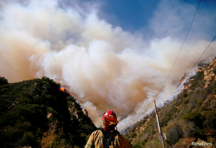 Firefighters battle the Woolsey Fire as it continues to burn in Malibu, California, Nov. 11, 2018.