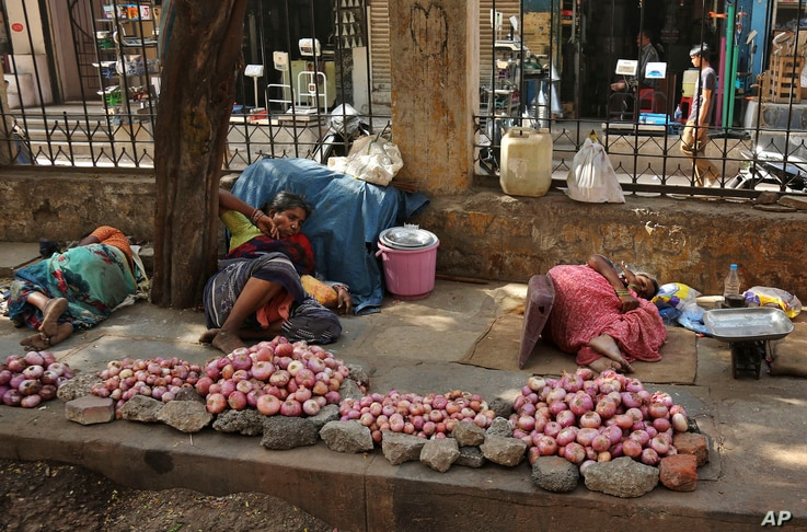 Indian vendors selling onions rest on a sidewalk under the shade of a tree on a hot summer day in Hyderabad, India, Monday, May 25, 2015. Hundreds of people have died since mid-April in a heat wave sweeping two southeast Indian states, Andhra Pradesh...