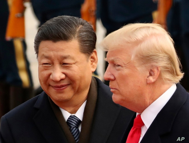 FILE - U.S. President Donald Trump and Chinese President Xi Jinping participate in a welcome ceremony at the Great Hall of the People in Beijing, China, Nov. 9, 2017.