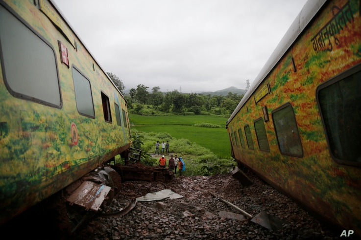 FILE - People look at derailed coaches of the Duronto Express in Asangaon, some 70 kilometers from Mumbai, India, Aug. 29, 2017.