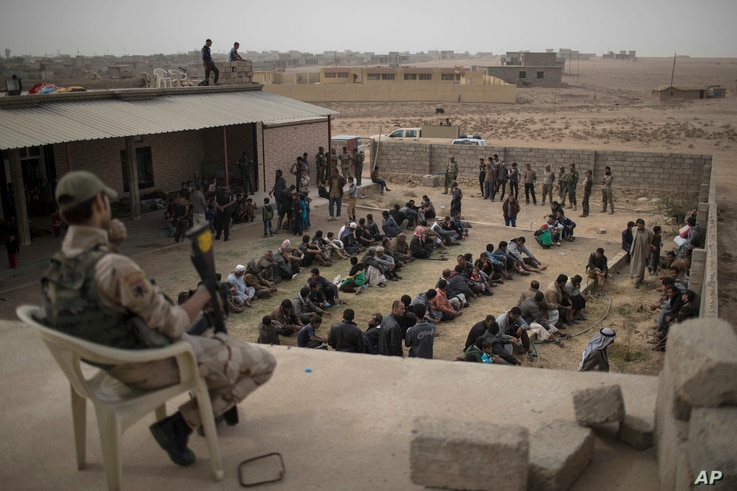 Displaced people who fled from Islamic State-held territory sit outside a mosque guarded by Iraqi soldiers in Shuwayrah, south of Mosul, Iraq, Nov. 1, 2016.