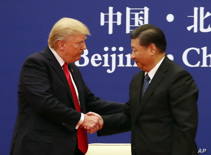 U.S. President Donald Trump and Chinese President Xi Jinping shake hands during a business event at the Great Hall of the People in Beijing, Nov. 9, 2017.