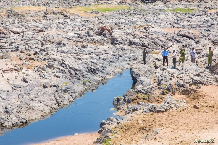 January Makamba, Tanzanian Minister of State for the Environment, and other officials inspect the dwindling water of the Ruaha River, in Kilolo district, Tanzania, Oct. 19, 2016.