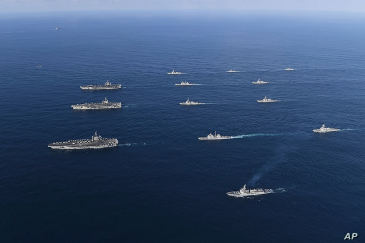 In this Nov. 12, 2017 photo provided by South Korea Defense Ministry, three U.S. aircraft carriers USS Nimitz, left top, USS Ronald Reagan, left center, and USS Theodore Roosevelt, left bottom, participate with other U.S. and South Korean navy ships ...