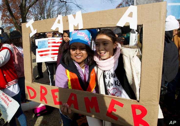 Demonstrators Karina Velasco, left, and Gabi Sanchez hold a sign during an immigration rally in support of the Deferred Action for Childhood Arrivals (DACA), and Temporary Protected Status (TPS), programs, on Capitol Hill in Washington, Dec. 6, 2017....