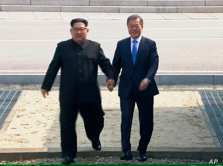 In this image taken from video provided by Korea Broadcasting System, April 27, 2018, North Korean leader Kim Jong Un, left, crosses the border into South Korea, along with South Korean President Moon Jae-in for their historic face-to-face talks, in