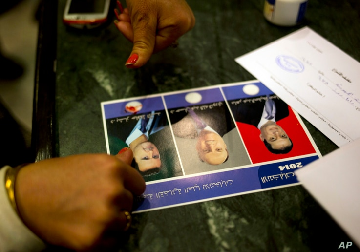 FILE - A woman votes for President Bashar Assad by marking the ballot with blood from her pricked finger, in Damascus, Syria, June 3, 2014.