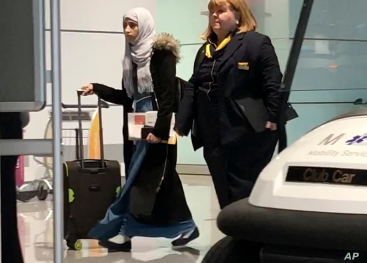 Yemeni national Shaima Swileh, left, walks through the airport in Munich, Germany, Dec. 19, 2018, before boarding a plane to the U.S., where she wants to give her son one more kiss before he dies.