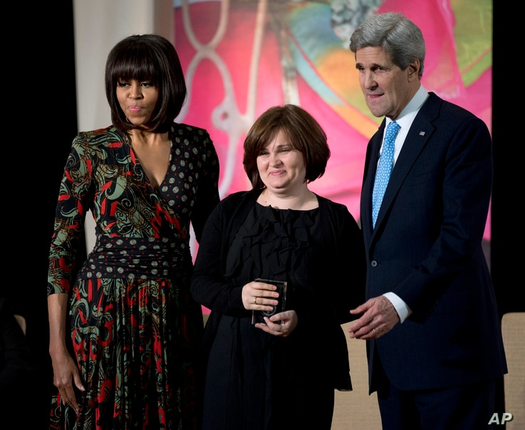 Then-First lady Michelle Obama, left, and Secretary of State John Kerry, right, honor Russian human rights activist, journalist Elena Milashina, with a Secretary of State's International Women of Courage Award during a ceremony at the State Departm...