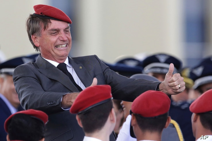 FILE - Presidential hopeful Jair Bolsonaro flashes two thumbs up as he poses for a photo with cadets during a ceremony marking Army Day, in Brasilia, Brazil, April 19, 2018.
