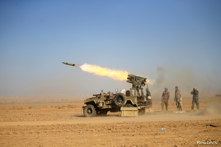 Shi'ite fighters fire a rocket toward Islamic State militants during a battle with Islamic State militants at the airport of Tal Afar west of Mosul, Iraq, Nov. 18, 2016.