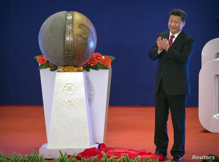 Chinese President Xi Jinping applauds after unveiling a sculpture during the opening ceremony of the Asian Infrastructure Investment Bank in Beijing, China, Jan. 16, 2016.