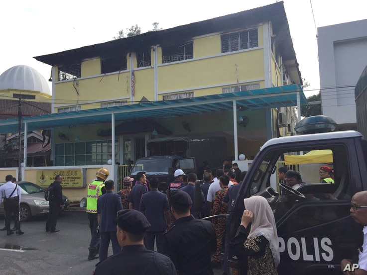 Police prepare to bring victims out of an Islamic religious school after a fire on the outskirts of Kuala Lumpur, Malaysia, Sept. 14, 2017. A fire department official in Malaysia said the fire at the school killed people, mostly teenagers.