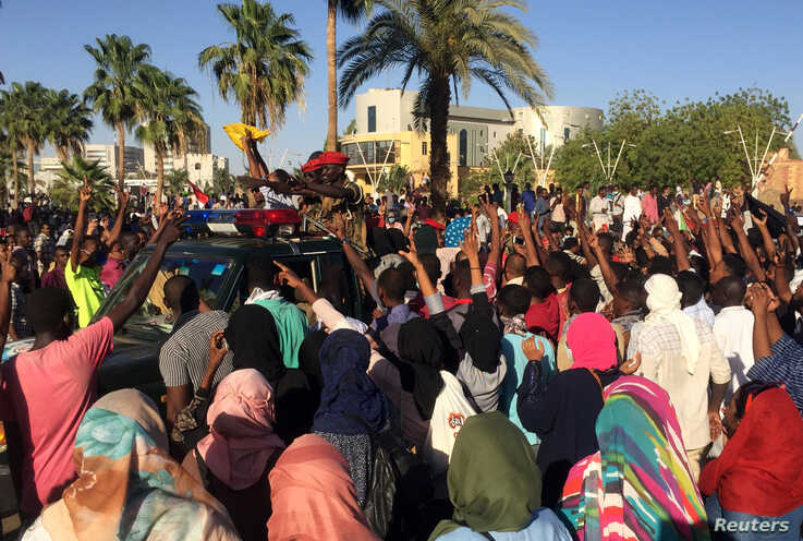 Sudanese demonstrators flash the victory sign as a military police vehicle drives past them during a protest demanding Sudanese President Omar Al-Bashir step down in Khartoum, Sudan, April 6, 2019.