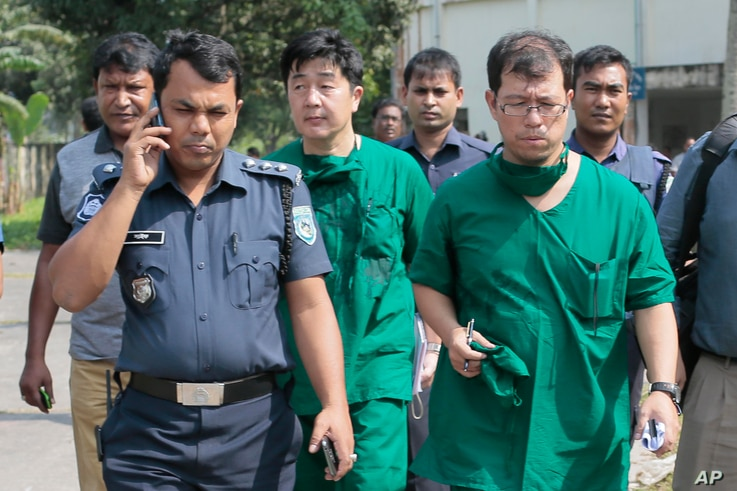 A Japanese doctor, front right, and the chief security officer of the Japanese embassy in Bangladesh, center, walk back from the morgue after the autopsy on the body of killed Japanese citizen Kunio Hoshi at Mahiganj village in Rangpur district, 300 ...