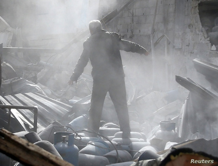 A man stands on the rubble of damaged buildings after an airstrike on the rebel-held town of Mesraba in the eastern Damascus suburb of Ghouta, Syria, Nov. 26, 2017.