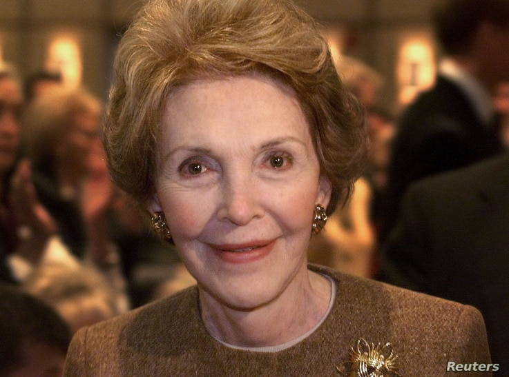 Former first lady Nancy Reagan smiles as she passes photographers after Texas Governor George W. Bush delivered his first major foreign policy speech at the Ronald Reagan Library in Simi Valley, California Novermber 18.