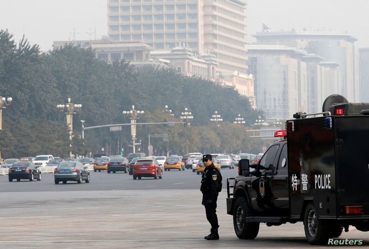 A Chinese policeman of the Special Weapons and Tactics (SWAT) team stands guard on a main street next to Tiananmen Square in Beijing, Oct. 31, 2013.