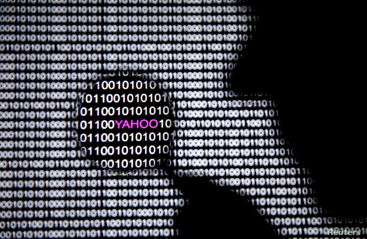 FILE - A photo illustration shows a man in front of a Yahoo logo seen through a magnifying glass in front of a displayed cyber code.