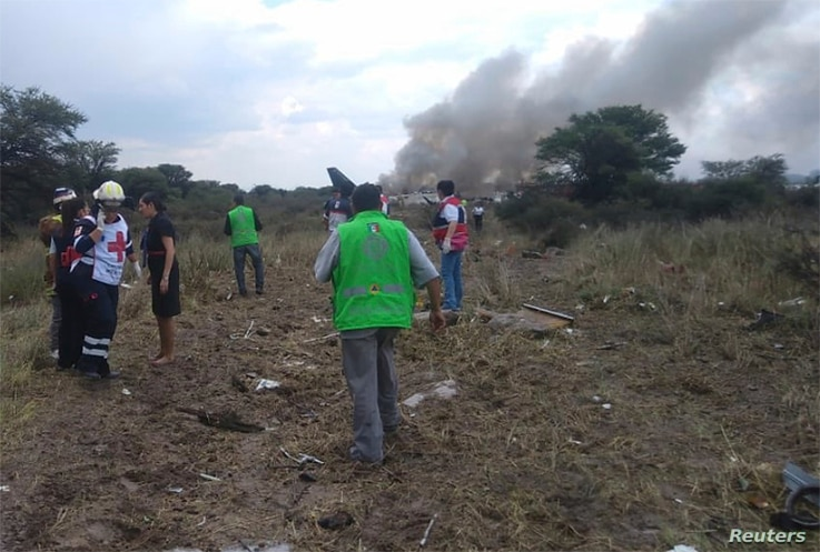 Rescue workers and firefighters are seen at the site where an Aeromexico airliner crashed in a field near the airport of Durango, Mexico, July 31, 2018.