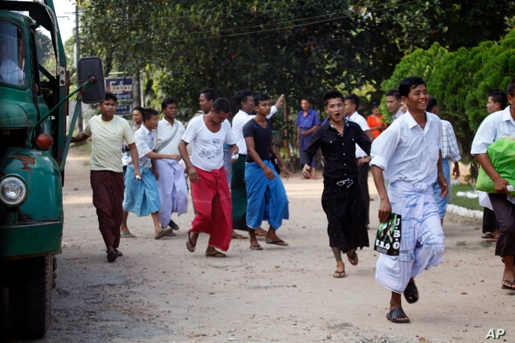 THIS CORRECTS SECOND SENTENCE - Myanmar prisoners get off at truck as they were released from Insein prison Tuesday, Oct. 7, 2014, in Yangon, Myanmar. The Myanmar government pardoned 3,073 prisoners on Tuesday, but advocacy groups said no political p...