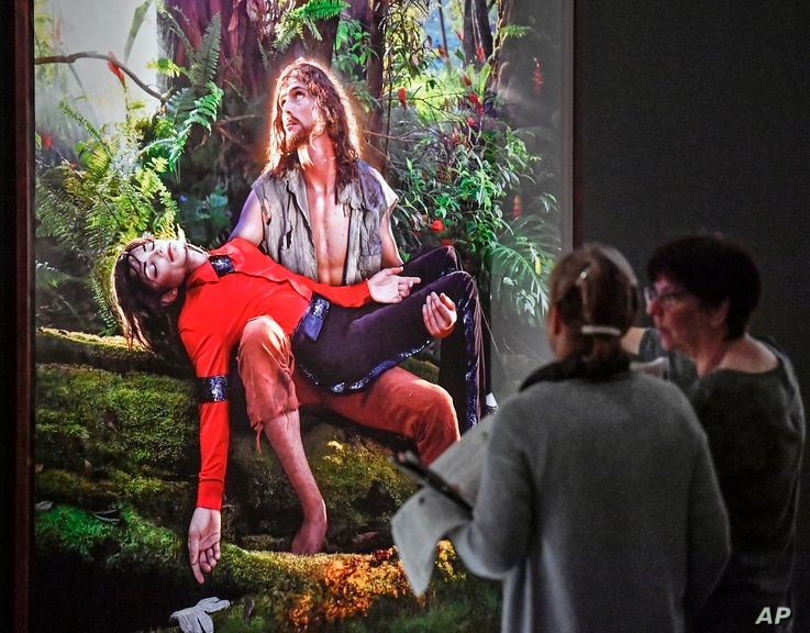 Visitors talk about the picture 'American Jesus: Hold me, carry me boldly' from US artist David LaChapelle at a preview of the exhibition 'Michael Jackson: On The Wall' at the Bundeskunsthalle museum in Bonn, Germany, March 21, 2019.