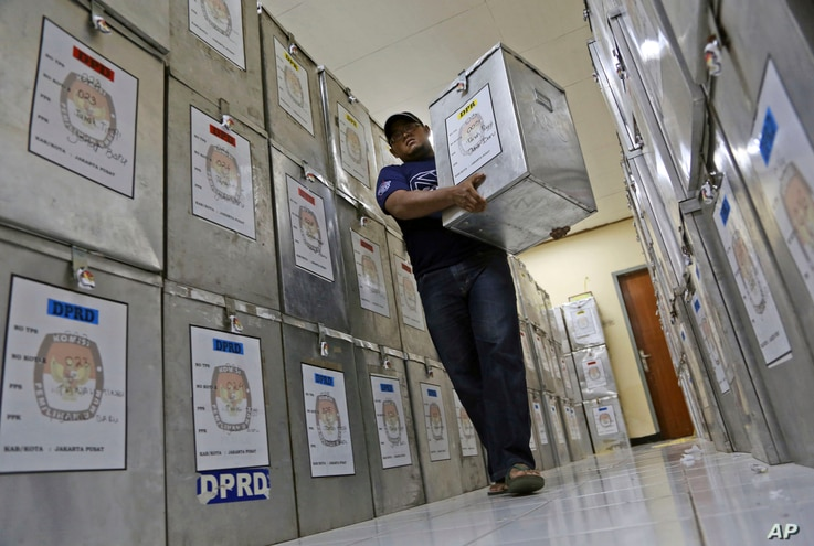 An Election Commission official walks among ballot boxes to be distributed to polling stations at a local government office in Jakarta, Indonesia, Tuesday, April 8, 2014. Indonesia, the world's third-largest democracy, is set to hold its legislative