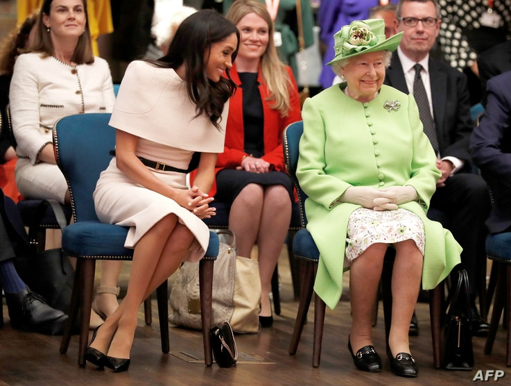 Britain's Queen Elizabeth II and Meghan, Duchess of Sussex gesture during their visit to the Storyhouse in Chester, Cheshire on June 14, 2018.