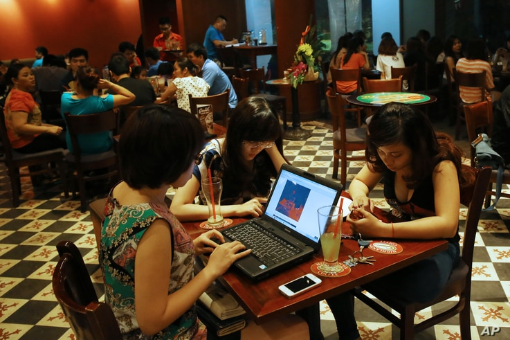FILE - Three young Vietnamese girls go online at a cafe in Hanoi, Vietnam, May 14, 2013. The country's potential for growth, young population and good Internet infrastructure have made it an attractive destination for regional and international inv...