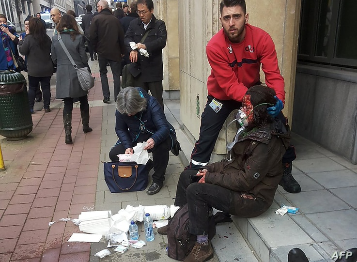 A private security guard helps a wounded women outside the Maalbeek metro station in Brussels on March 22, 2016 after a blast at this station located near the EU institutions.