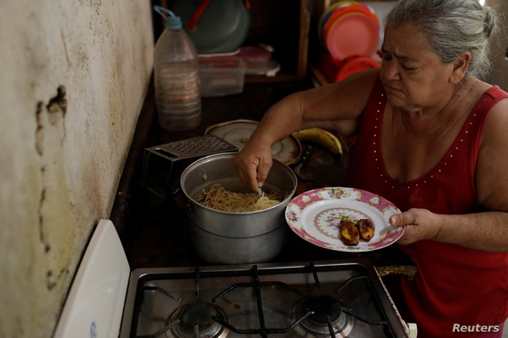 Antonia Torres, mother of Yuni Perez, cooks for seven people a packet of pasta received in a CLAP box, a Venezuelan government handout of basic food supplies, in her home at the slum of Petare in Caracas, Venezuela, March 9, 2018.