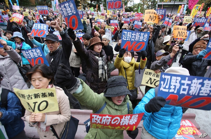 """FILE - Anti-U.S. base protesters hold placards with a slogan that reads: """"No to Henoko new base"""" during a rally in Tokyo."""