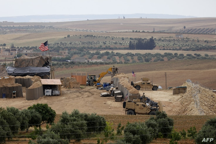 File photo taken on May 8, 2018, shows vehicles and structures of the US-backed coalition forces in the northern Syrian town of Manbij.