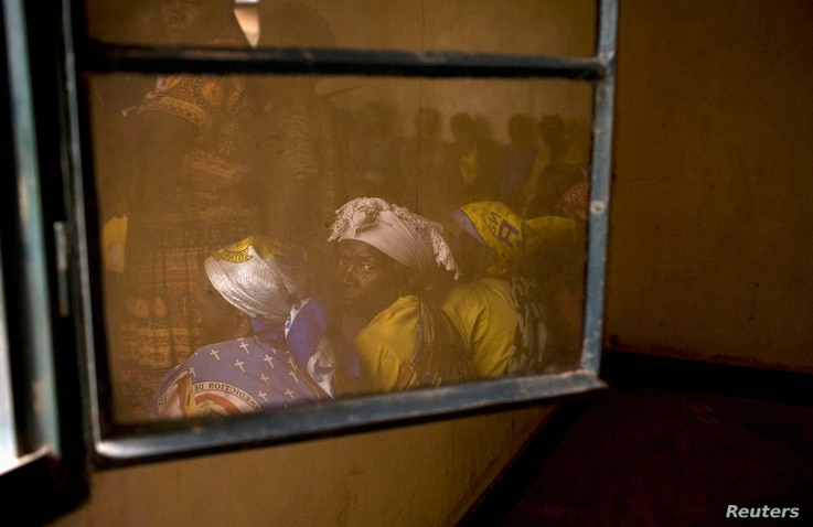 Members of Congolese Women's Association, who have been widowed by conflict, are reflected in a window during their meeting in the town of Rutshuru in North Kivu, east of the Democratic Republic of Congo, May 2012.